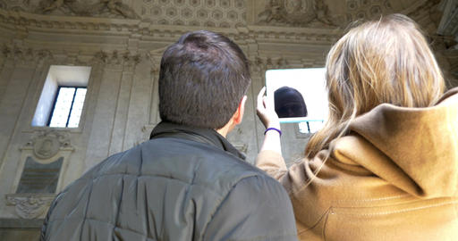 Two people making photos with pad inside ancient building Live Action