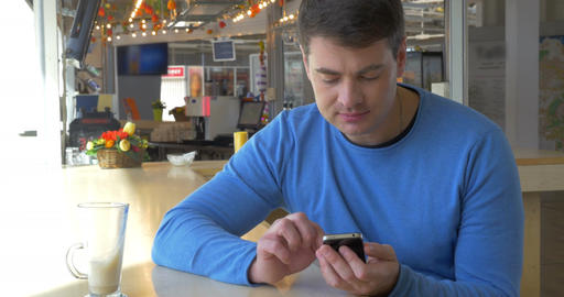 Man Sitting in Coffee Shop with Smartphone Footage