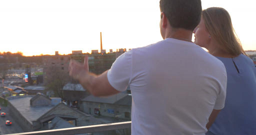 Romantic Couple On The Balcony Look At The City At Sunset Footage