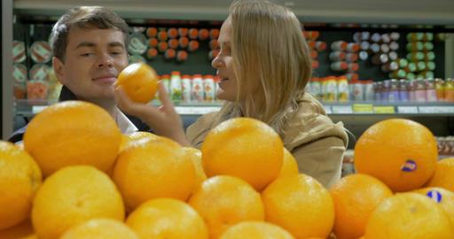 Man and woman choosing oranges Footage
