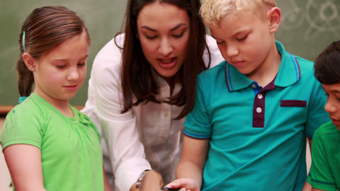Pupils an teacher looking at rock with magnifying glass Footage