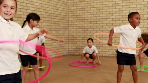 Pupils exercising with hula hoop Footage