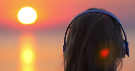 Girl listening to music and looking at sunset scene Footage