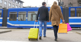 Couple with suitcase and shopping bags crossing the road Footage