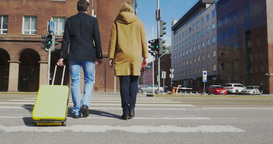 Man and woman with suitcase crossing the road Footage