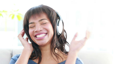 Woman with headphones listening to music on the sofa Footage