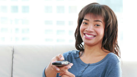 Attractive woman holding a remote sitting on the sofa Footage