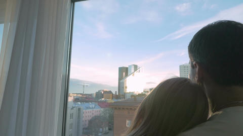 Young couple looking at big city through the window Live Action