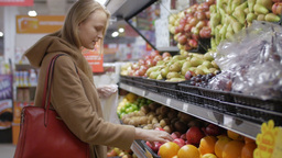 Young woman choosing fresh fruit in the supermarket Footage