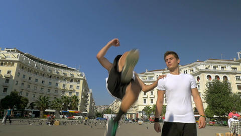 Young man doing somersaults in the street Footage