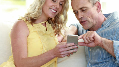 Happy couple using smartphone on sofa Footage