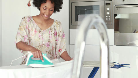 Smiling woman ironing her clothes Footage