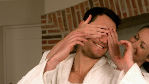 Pretty woman covering her boyfriends eyes with her hands Footage