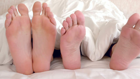 Bare feet of gay men couple in bed Footage