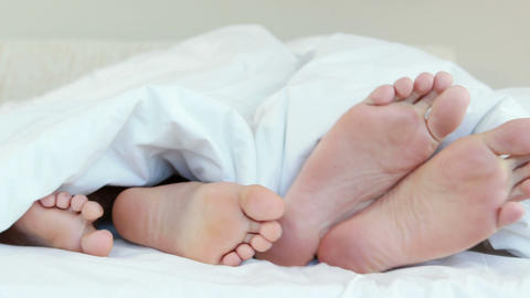 Two pairs of feet in bed crossing over each over Footage