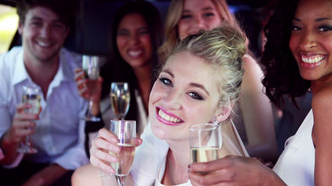 Happy friends drinking champagne in limousine Footage