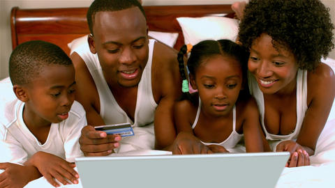 Black family on bed with laptop and credit card rejoicing Live Action