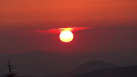 Red globe of the sun goes down behind the mountain 11a Footage