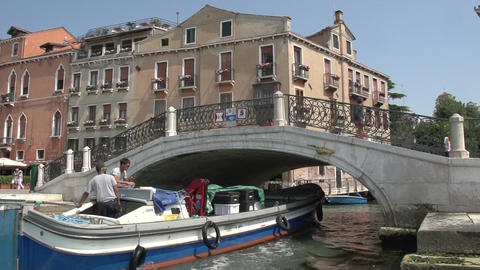 People walking over bridge of San Marco Square, boat passing by in slow motion Footage