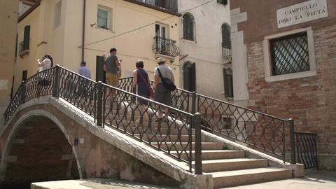 People walking over love locks bridge at Campiello Drio La Pieta Footage