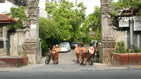 Boys and girls in brown uniform in front of balinese school gate ライブ動画