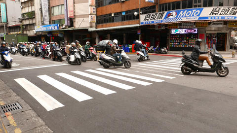 Many motorbikes stand at street intersection, start to move on green light Footage