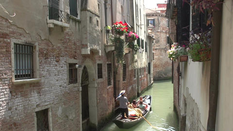 Narrow canal with a gondola and houses in Venice Footage
