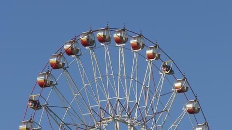 Ungraded: Ferris Wheel At Amusement Park Against Blue Sky stock footage