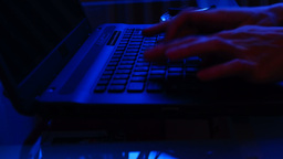 Close up female hands typing on laptop keyboard in the evening