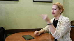 Young woman using tablet PC, then put it aside and look straight, side view Footage