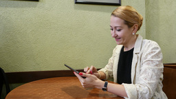 Girl sit at table, browse on tablet PC, simple cafe room. Watch fun thing smile Footage