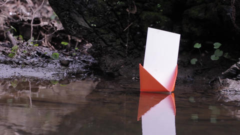 Orange paper boat floating on the water of a small creek 88a Footage