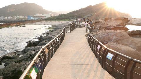 Asian tourists at Yehliu Geopark walkway, sunset star beam, POV walk Footage