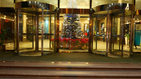 Christmas decoration fir tree in night, through glass wall, revolving doors Footage
