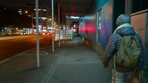 Night urban construction area, following man with backpack, red flash in front Live Action