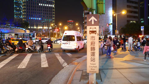 Ambulance car pass intersection, busy traffic junction at night time Footage
