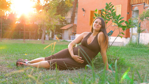 Happy Pregnant woman in garden at sunset Stock Video Footage