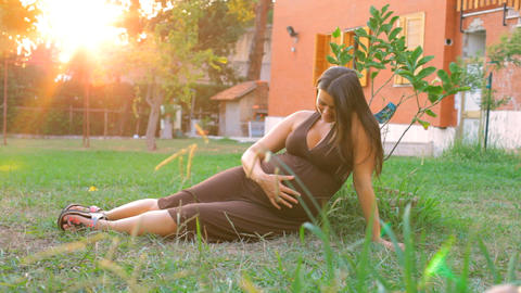 Happy Pregnant woman in garden at sunset Footage