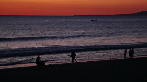 People silhouettes on the sunset beach with red sky and... Stock Video Footage