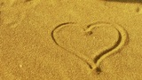heart on golden sandy beach,wind blow sand Footage