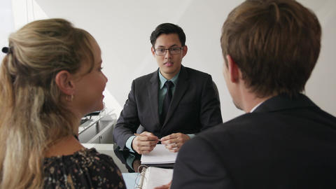 16 Young Couple Talking With Financial Advisor In Modern Office Footage