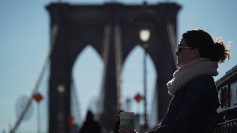 A young woman is enjoying a hot drink on a cool day on the Brooklyn Bridge Footage