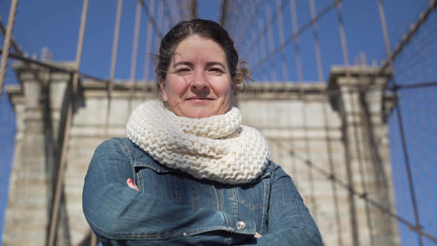A beautiful young woman enjoys a moment on the Brooklyn Bridge Footage
