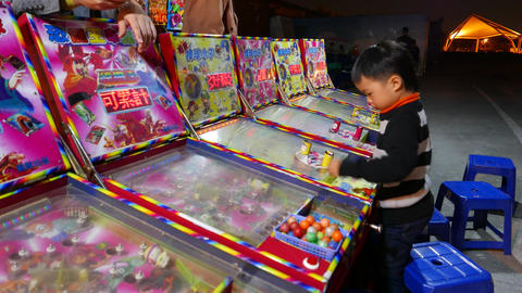 Little asian boy confused, playing gaming machine, pinball Footage