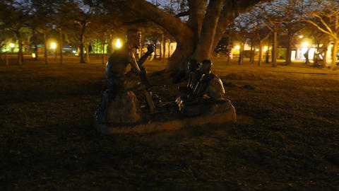 Sculpture composition father and two children, night park, parallax shot Footage