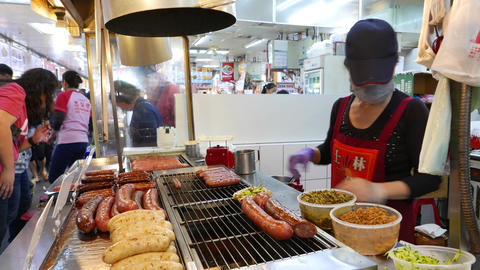 Making hot-dog with fresh sausage, food court at Shilin market ビデオ