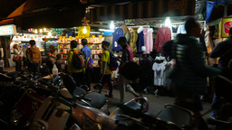 Tracking shot, silhouettes against clothing shop at night market street Footage