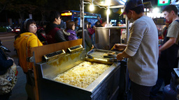 Cistern with boiling oil, man frying whole fish inside, night market booth Footage