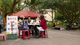 Open air eatery in park, woman sitting at a table on the street Footage