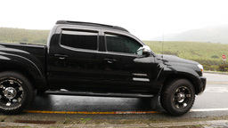 Black 4x4 car take out and drive away, side view, follow camera Footage